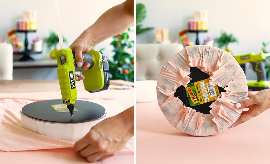 Một người phụ nữ dùng keo nóng để cố định vải vào chiếc đệm tròn 10 inch.