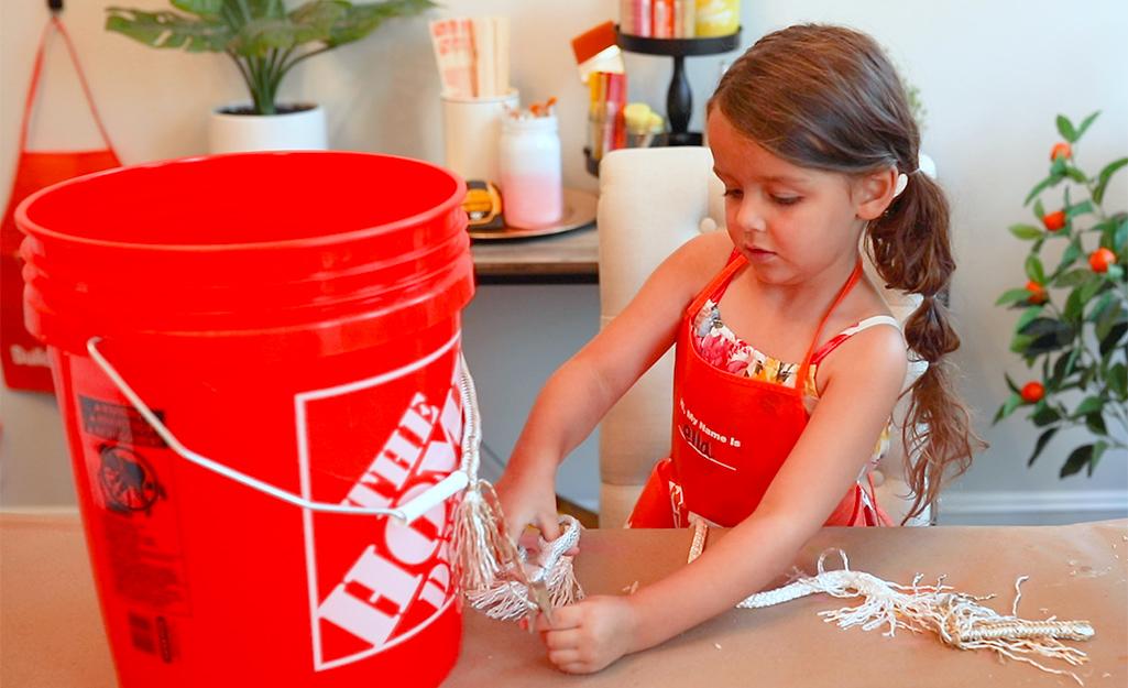 Một đứa trẻ quấn tay cầm xô bằng dây nylon.