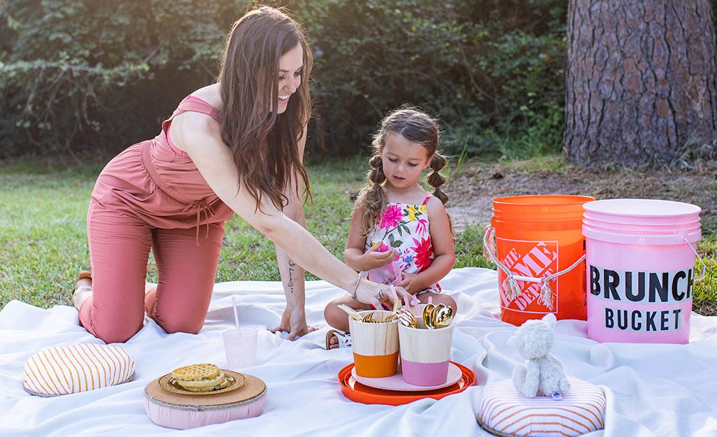 Một người phụ nữ và một đứa trẻ đang tận hưởng bữa ăn ngoài trời với một xô nửa buổi.