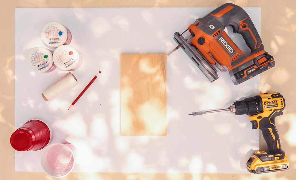 Cốc đỏ, gỗ và các dụng cụ nằm trên bàn.