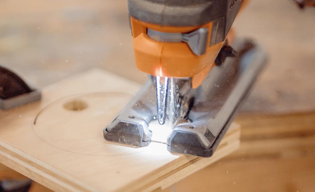 Một người nào đó sử dụng ghép hình để cắt một hình tròn trong một miếng gỗ.