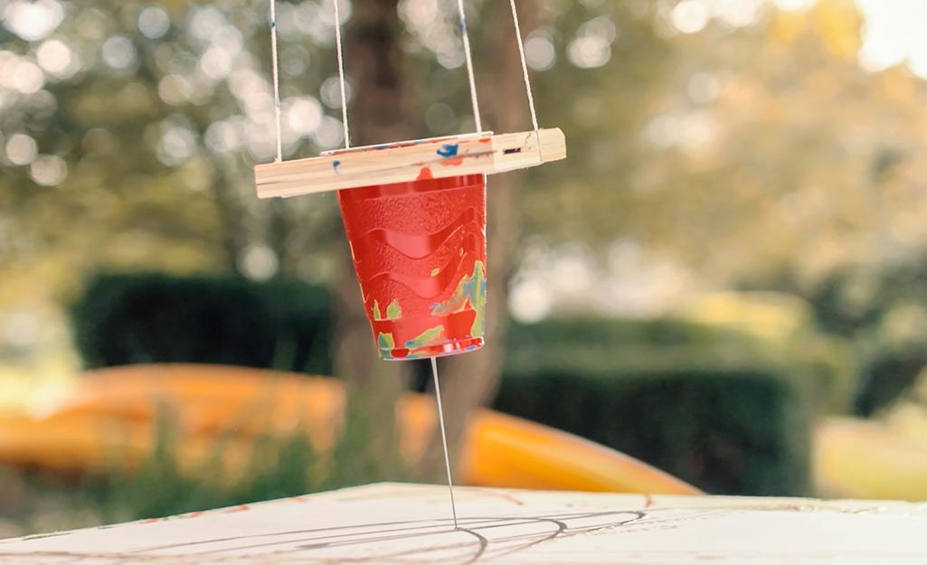 Một cốc sơn đong đưa trong một con lắc tự chế.