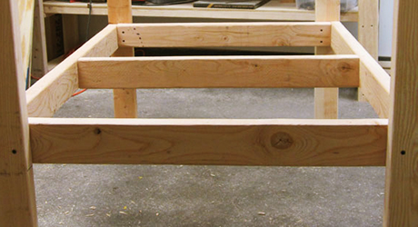 Chicken coop floor frames attached to legs.