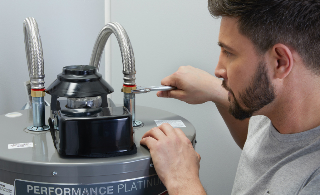 A person adjusts a water heater with a wrench.