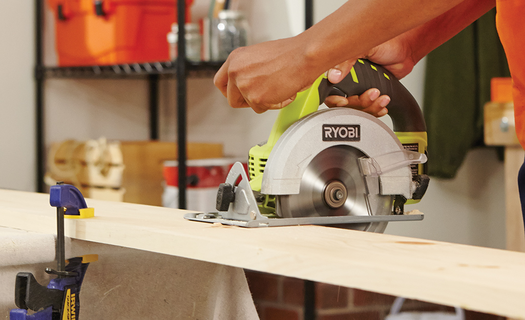 a person using a saw to cut plywood