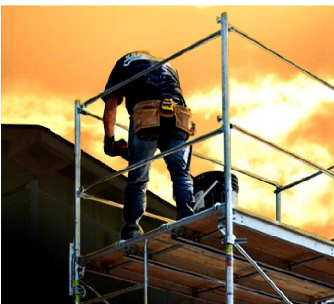 A Construction Worker Stands on a Platform