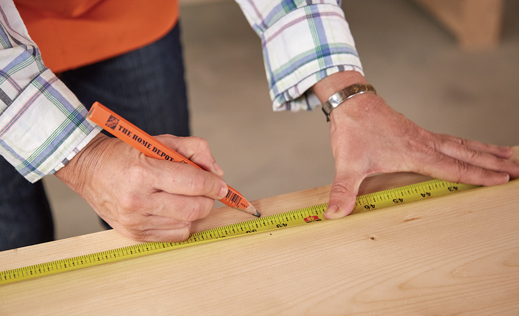 A woman uses a measuring tape and pencil to mark cuts on a wood board.