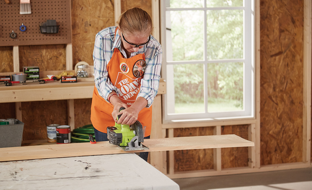 A woman uses a circle saw to cut a wood board.
