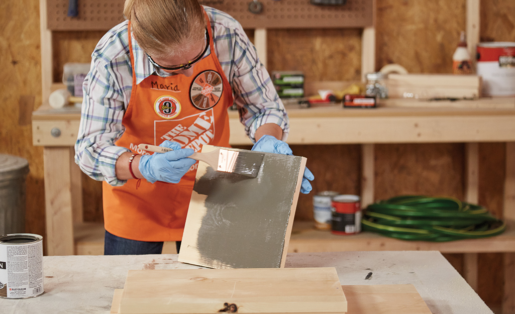A woman paints a cut wood board.
