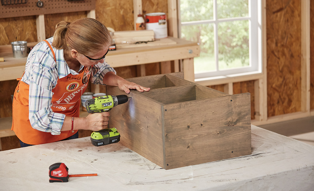 A woman uses a power drill to screw together wood boards into a cube organizer.