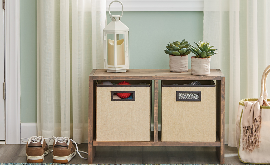 A cube organizer with two fabric cubes sits in a home entryway.