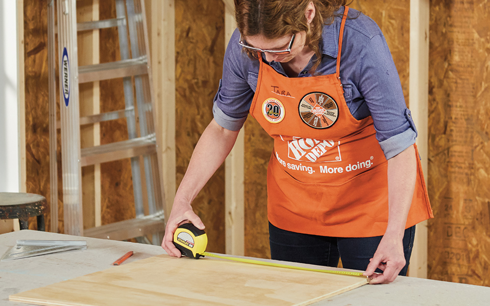 A woman measuring a piece of wood.
