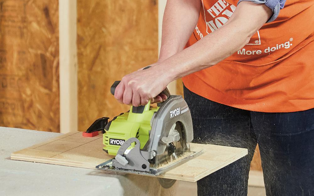 A woman cutting wood with a circular saw.