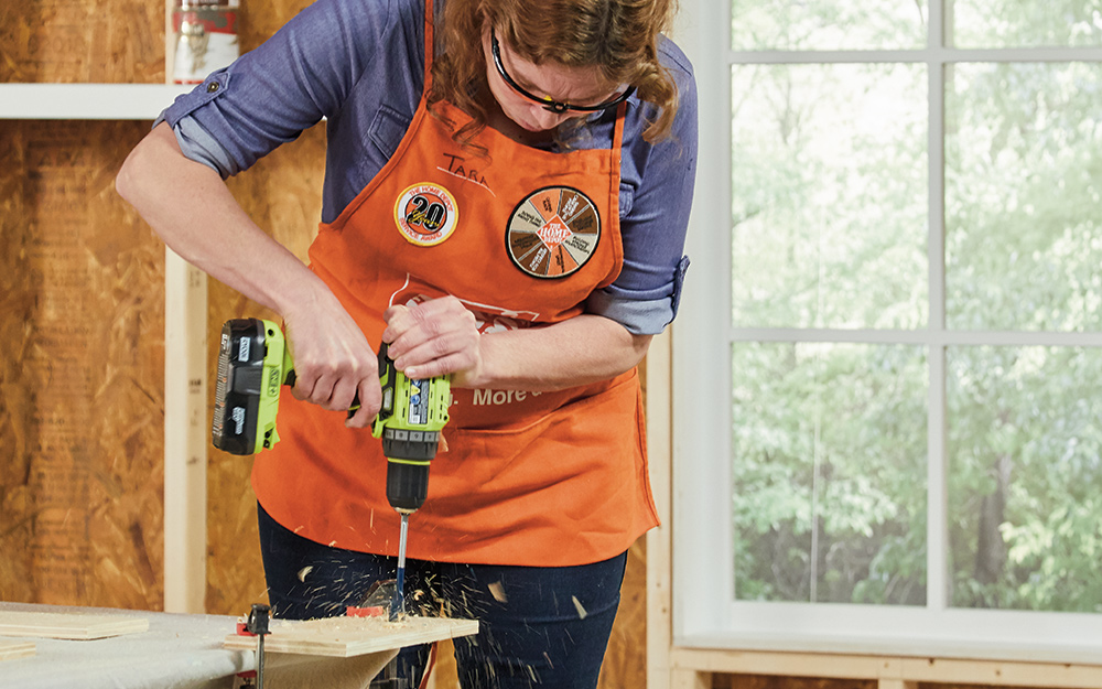 A woman drilling into wood.