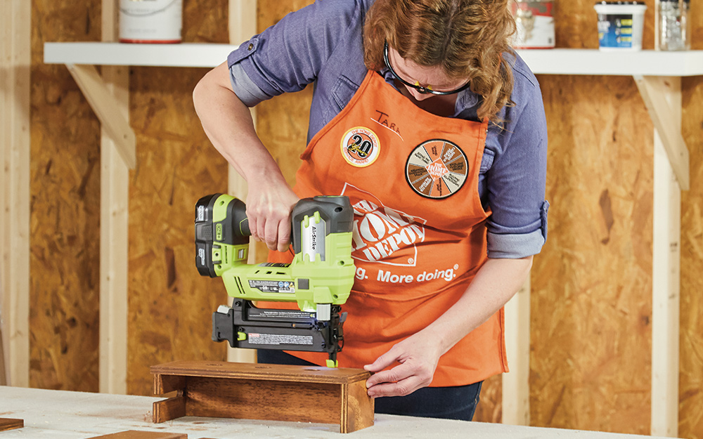 A woman using putting nails into a box with an electric nail gun.