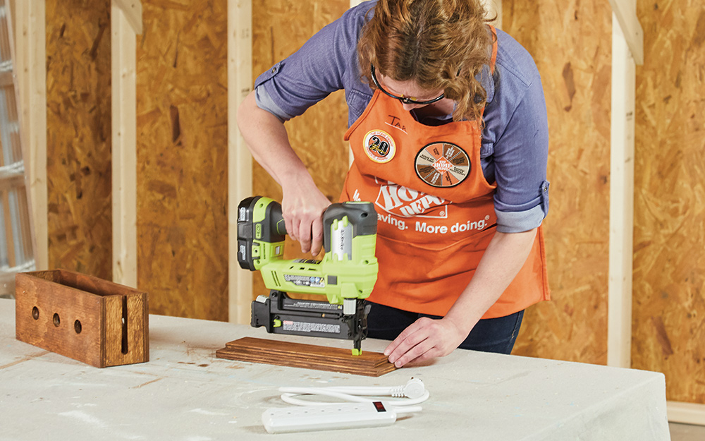A woman putting a nail into a piece of wood with an electric nail gun.