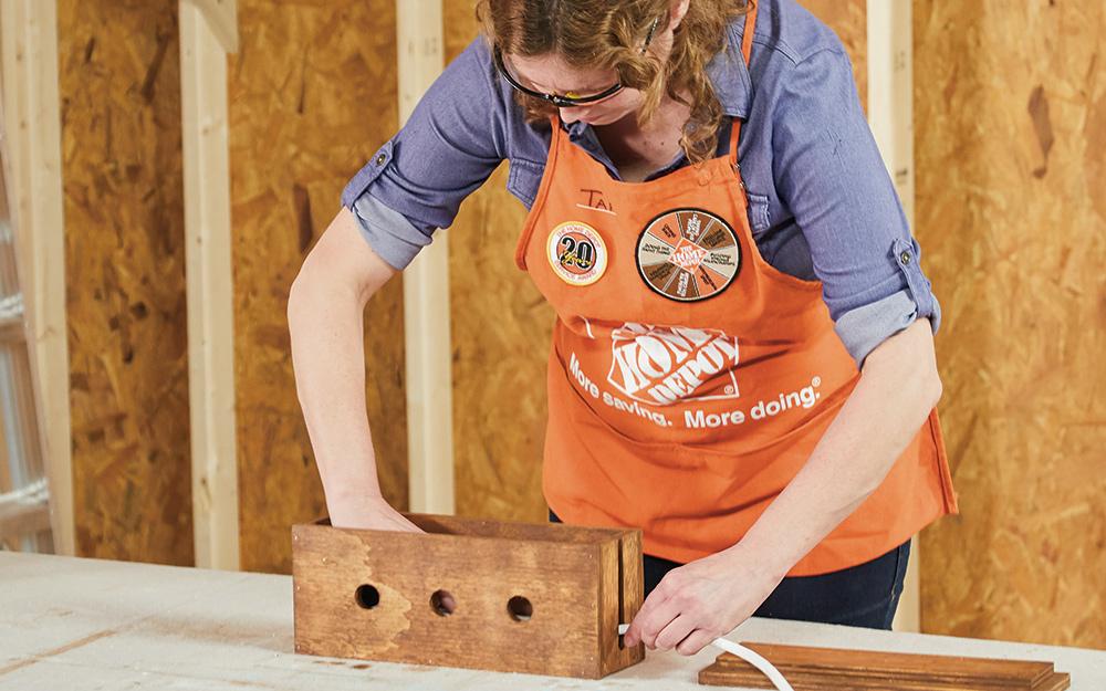 A woman putting a cord through a slot in a wood box.