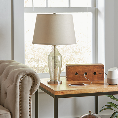 A wood charging station next to a lamp on a table