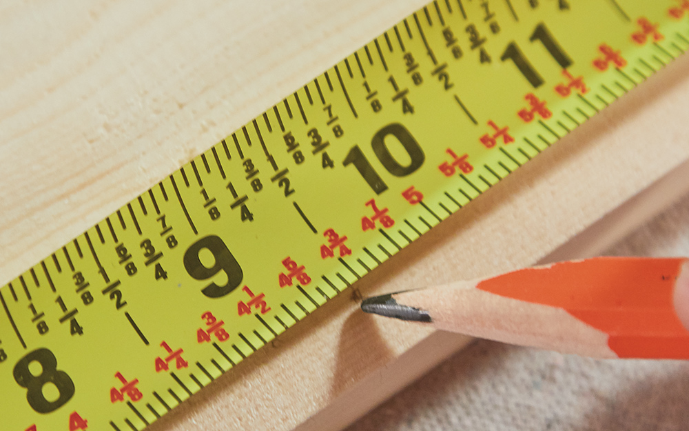 A tape measure and pencil being used to mark the wood.