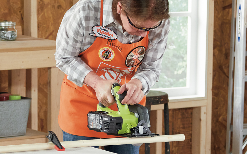 A woman cutting wood with a power saw.