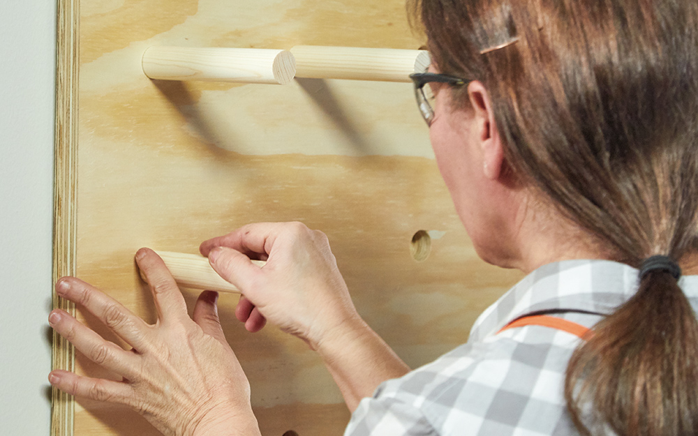 A woman inserting pegs to hold shelves on the pegboard.