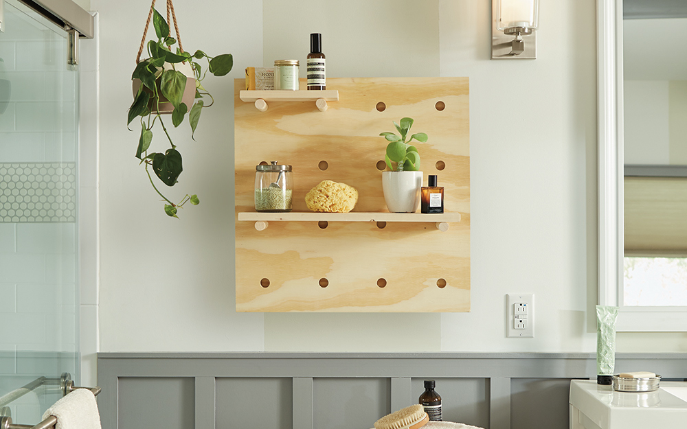 A pegboard shelf hangs on the wall of a bathroom.
