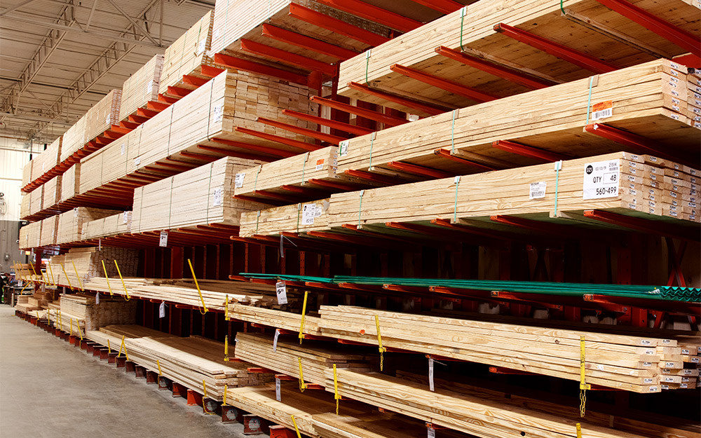 Different varieties of lumber sit on a shelf inside The Home Depot.