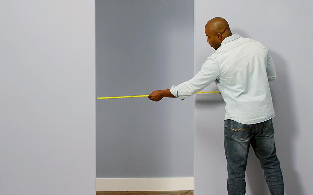 Man measures the opening of the doorway.