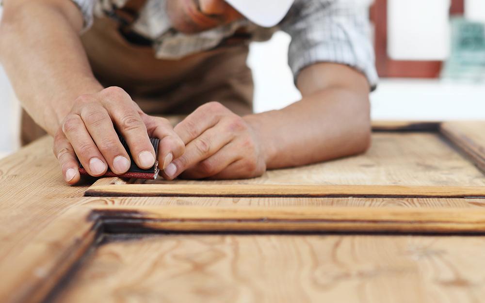 A man creates pattern on a barn wood door.