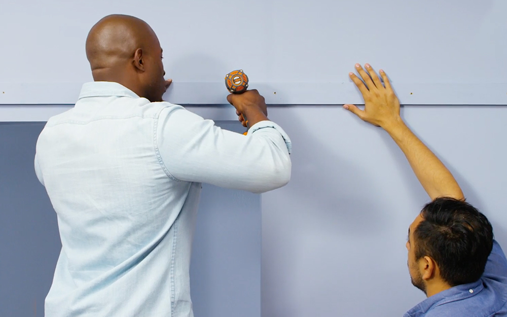 Two men install support moulding.