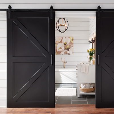 A black farmhouse-style barn wood door is the entry for a master bath.