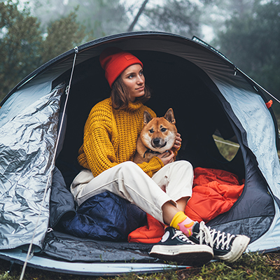 A woman and a dog look out of a tent while camping.