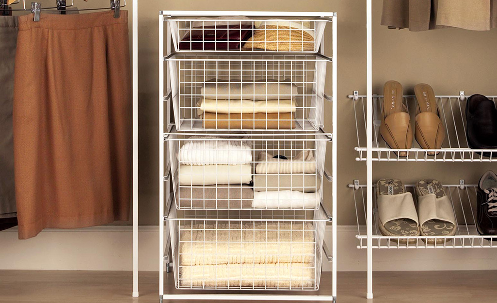A freestanding organizer filled with four wire baskets in a closet.