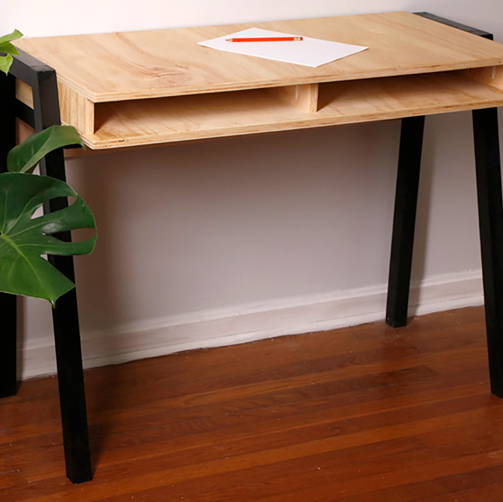 A blank piece of paper and an orange pencil rest on the wooden top of a DIY desk that has black legs.