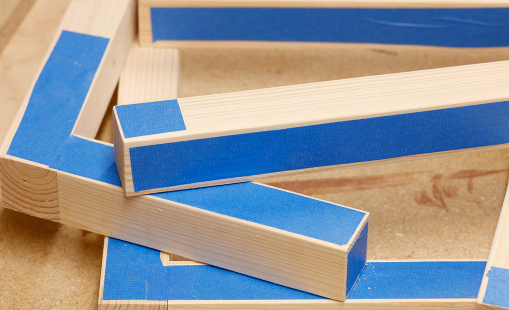 Blue painters tape covers some of the wooden pieces of a DIY desk project before they are assembled.