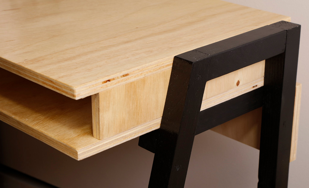 Black legs are attached to the side of a wooden box that serves as the body of a DIY desk.