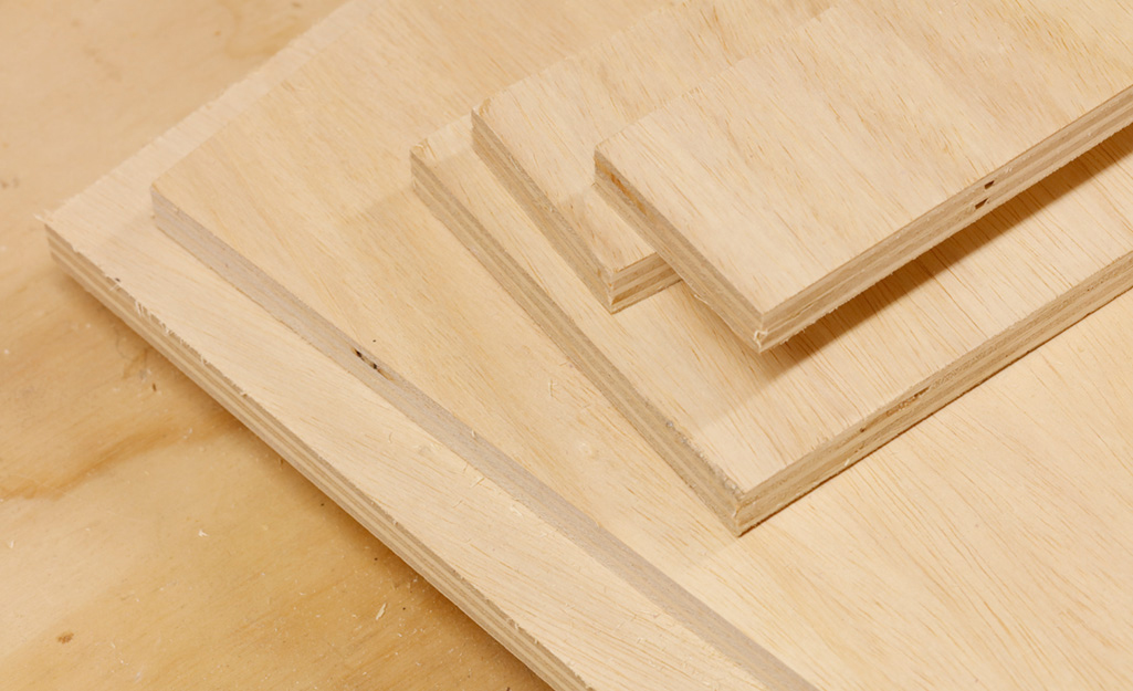 Cut pieces of plywood are ready to be used for a DIY desk project.