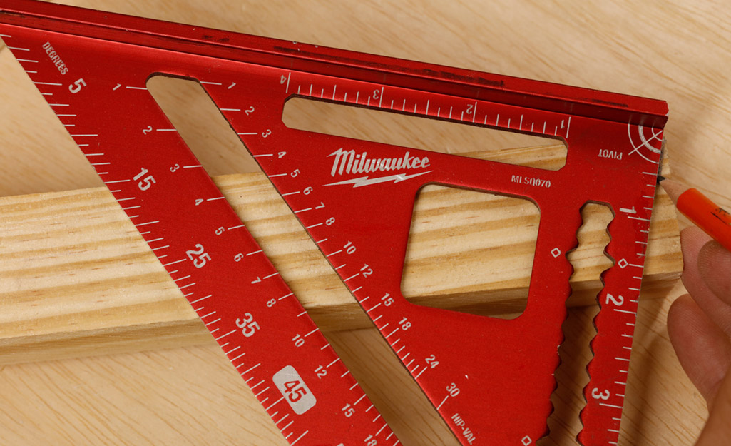 A person uses a pencil and a red speed square to mark measurements on a piece of wood.