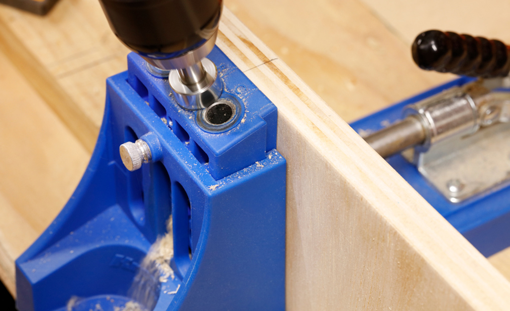 A drill is used to make pocket holes in plywood for a DIY desk project.