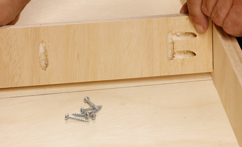 Screws are used to connect the pieces of the top of a DIY desk.
