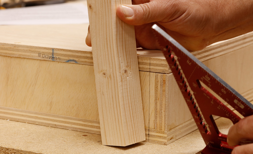 A person begins attaching legs to the wooden box of a DIY desk, which has been placed upside down.