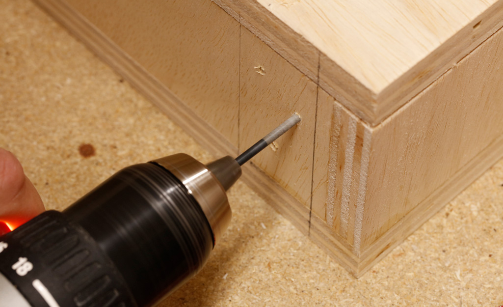 A drill is used to make freehand pocket holes near the corner of the wooden box of a DIY desk.