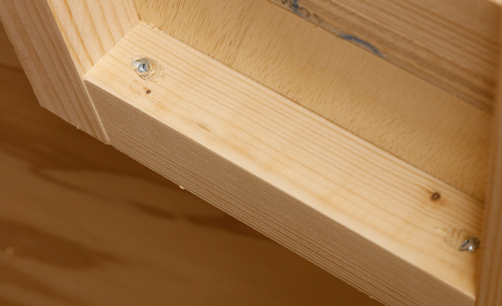 Screws are used to attach a piece of plywood that serves as rear support to a DIY desk
