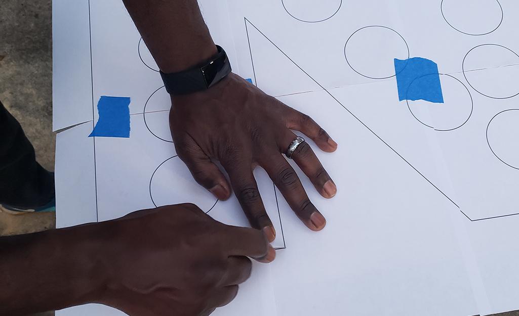 A person making a paper stencil letter.