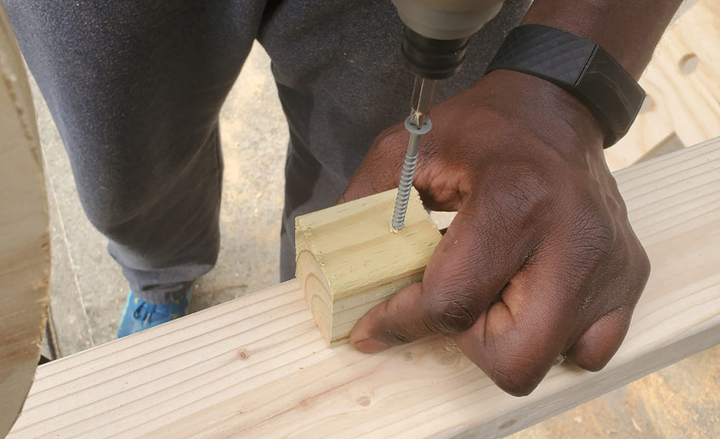 A person drilling a small block into a 2 x 4 board.
