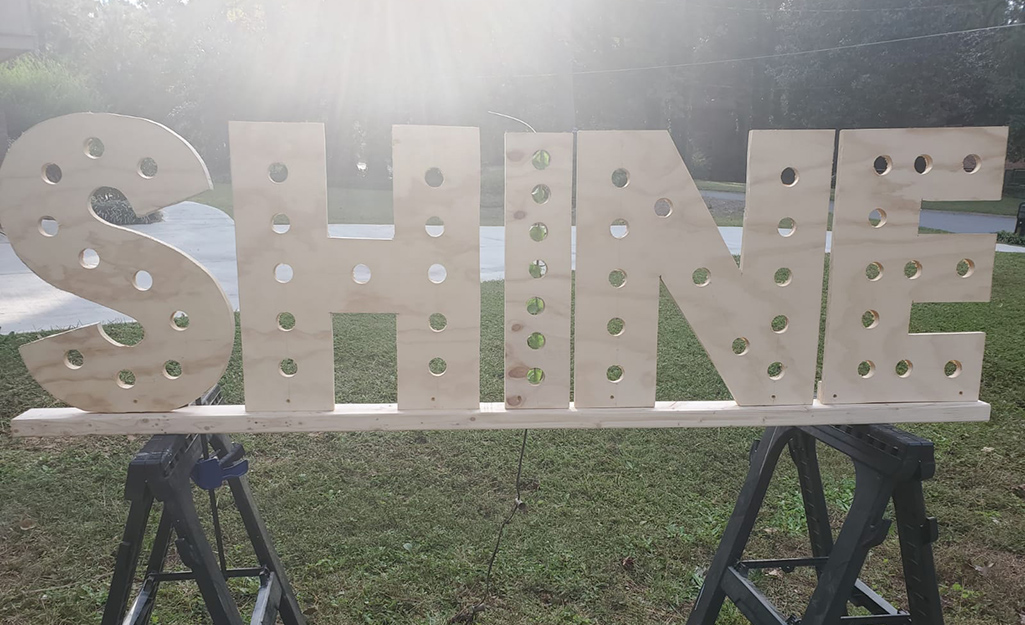 """A plywood letter sign that reads """"SHINE."""""""