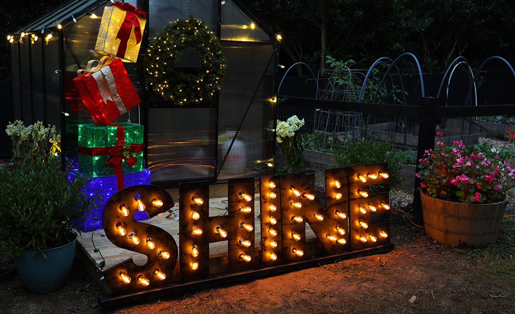 """An illuminated faux marquee letter sign reading """"SHINE"""" in front of a greenhouse decorated for Christmas."""