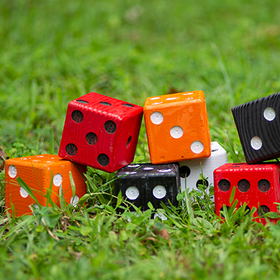 Large red, orange, black and white dice stacked on a lawn.