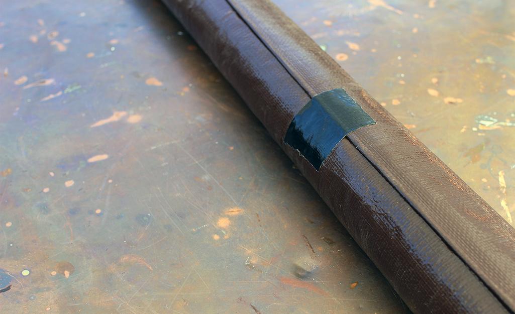 Màn chiếu tự làm được cuộn lại để cất giữ và được bảo vệ bằng băng dính không thấm nước.