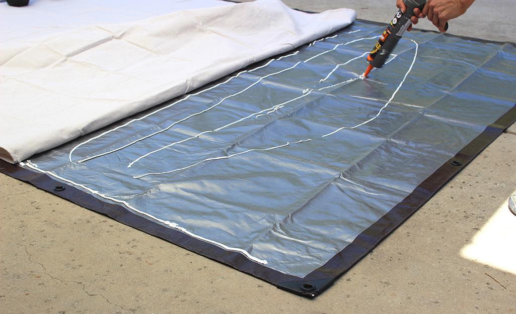 Một người sử dụng chất kết dính để nối phần trên và phần dưới của màn hình chiếu DIY.